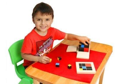 Niño trabajando con el cubo del trinomio montessori