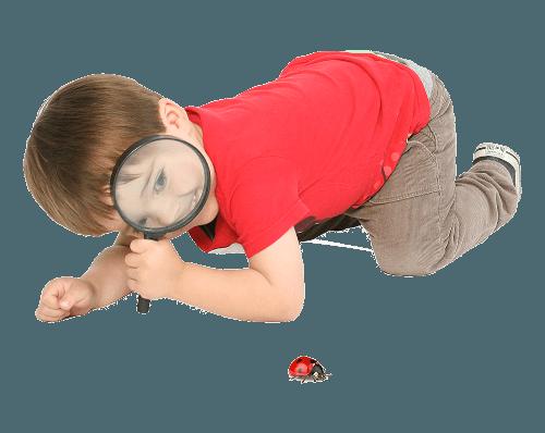 Niño Montessori con lupa explorando la naturaleza